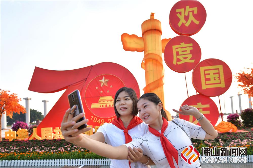 """市民在""""欢度国庆""""的雕塑前合影。谭杰才/摄"""