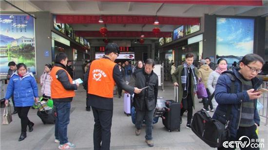 青年志愿者到车站出站口,发放《服务指南》及列车时刻表.(央视图片